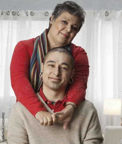 Hispanic mother hugging adult son