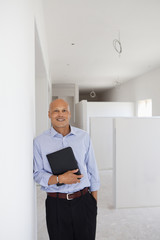Hispanic architect holding digital tablet in unfinished room