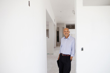 Hispanic architect leaning on wall in unfinished room