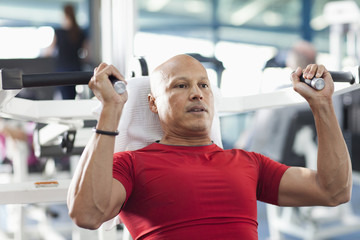 Mixed race man exercising in health club