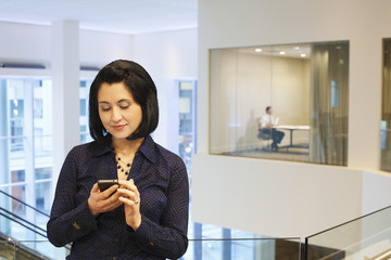 Mixed race businesswoman text messaging on cell phone in office