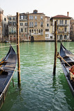 Gondolas moored in canal on wooden posts