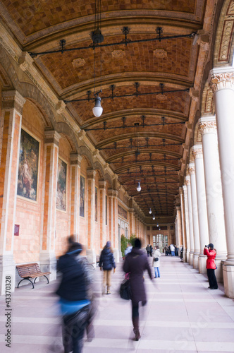People walking underneath ornate portico