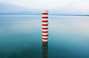 Red and white stripe pillar in tranquil lake