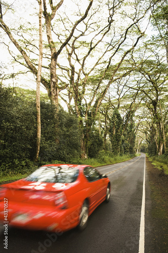 Red car driving down country lane