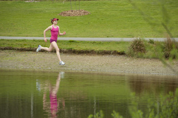 Mixed race woman running near pond
