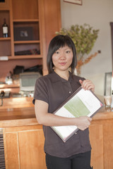 Chinese waitress holding menus in restaurant