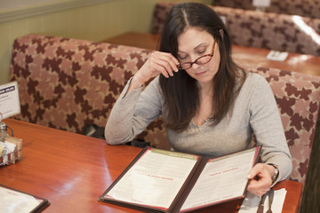Caucasian woman looking at menu in restaurant