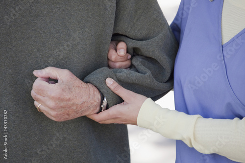Nurse supporting senior man