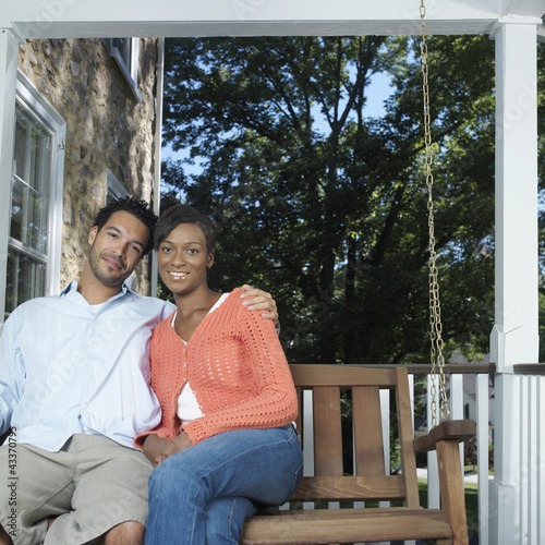 Mixed race couple sitting on porch swing