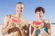 Mixed race couple eating watermelon on beach