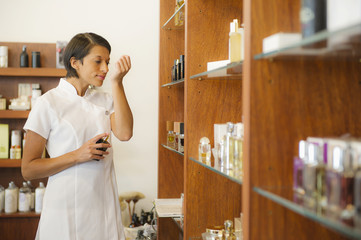 Aesthetician smelling scent in beauty product store