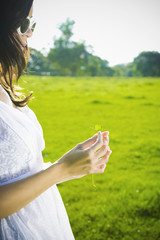 Hispanic woman holding four-leaf clover in park