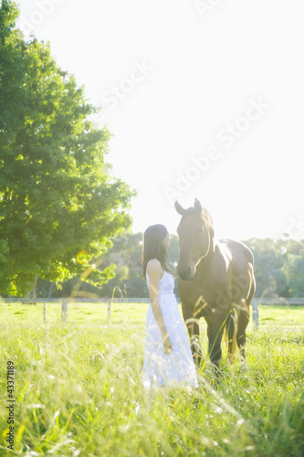 Hispanic woman standing with horse in pasture