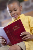 Mixed race boy reading bible