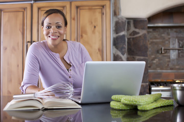 African American woman using laptop in kitchen