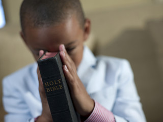 Mixed race boy praying with bible