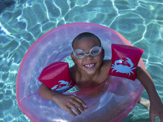 Mixed race boy floating on inflatable ring in swimming pool