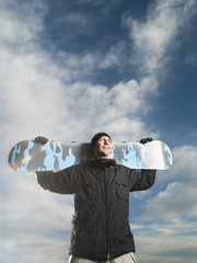 Caucasian man holding snowboard
