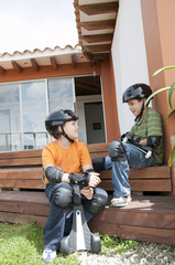 Hispanic boys in pads and helmets holding skateboards