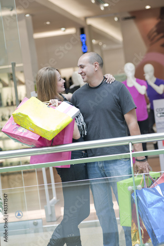 Hispanic couple standing in mall holding shopping bags
