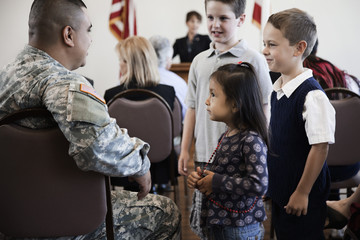 Children talking to soldier at political gathering