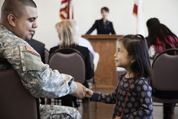 Soldier shaking girl's hand at political gathering
