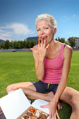 Woman eating chocolate candy after workout