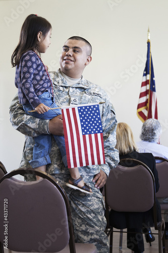 Hispanic soldier holding daughter at political gathering