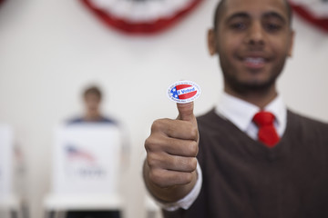 Hispanic voter holding an I Voted sticker in polling place