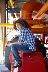 Mixed race teenager sitting on machinery