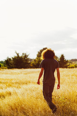 Mixed race teenager walking in remote field