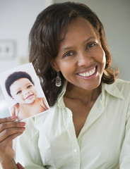 Black woman holding photograph of baby