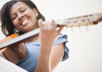 Black woman playing guitar