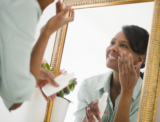 Black woman applying moisturizer