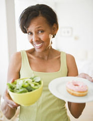 Black woman holding salad and donut