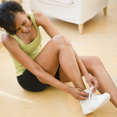 Black woman putting on athletic shoes