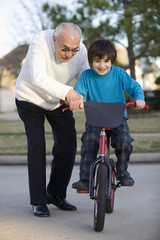 Hispanic grandfather teaching grandson to ride bicycle