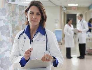 Hispanic doctor holding medical record