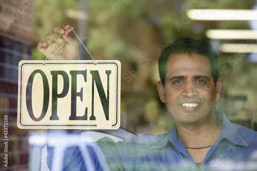 Indian man hanging open sign