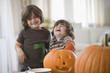 Mixed race brothers carving Halloween pumpkins