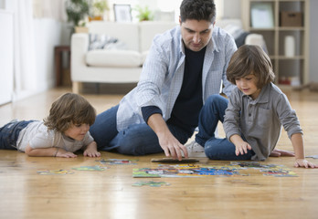 Mixed race father and sons putting together puzzle on floor
