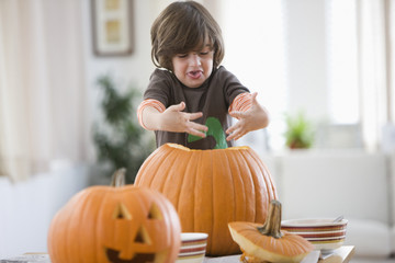 Mixed race boy carving Halloween pumpkins