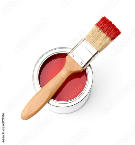Full of red paint tin and paint brush on it, isplated on white