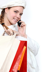 young woman holding shopping bags and talking on her  cell