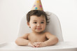 Mixed race girl sitting in high chair wearing party hat