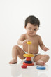 Mixed race baby girl playing with stacking toy