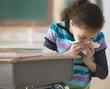 Hispanic girl blowing nose in classroom
