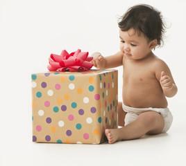 Mixed race baby girl opening birthday gift