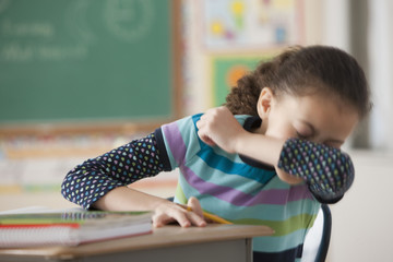 Hispanic girl sneezing in classroom